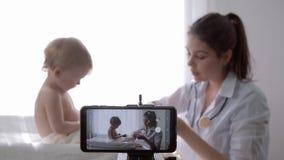 Blogging, popular vlogger female doctor filming new episode for vlog on smartphone during medical examination of baby stock footage