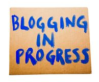 Blogging in progress on placard. Blogging in progress text on a placard isolated over white Royalty Free Stock Photos