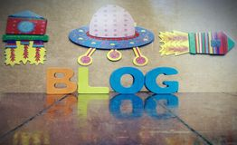Blogging with space ships. Space ships rocket and the word BLOG with wooden letters on an pld wooden floor wit reflection Royalty Free Stock Photos