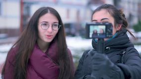 Two brunette girls friends and bloggers recording video by camera in winter travel stock footage