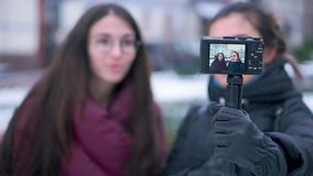 Two brunette girls friends and bloggers recording video by camera in winter travel. Blogging technology and leisure concept stock video