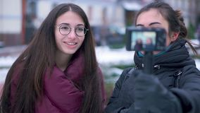 Two brunette girls friends and bloggers recording video by camera in winter travel. Blogging technology and leisure concept stock video footage