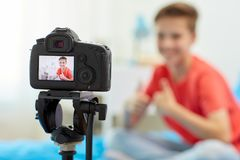 Camera recording video of blogger boy at home. Blogging, technology and people concept - camera recording video of happy smiling blogger boy showing thumbs up at royalty free stock image
