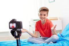Happy boy with camera recording video at home. Blogging, technology and people concept - happy smiling boy or blogger with camera recording video at home royalty free stock photos