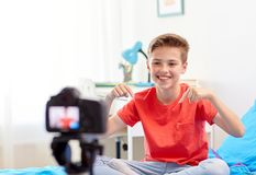 Happy boy with camera recording video at home. Blogging, technology and people concept - happy smiling boy or blogger with camera recording video at home stock photography