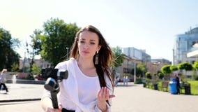 Blogging Vídeo do película da mulher na câmera na rua video estoque