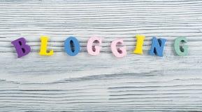 BLOGGING Wort auf dem hölzernen Hintergrund, der von buntem ABC-Alphabet verfasst wird, blockieren hölzerne Buchstaben, Kopienrau Stockfotos