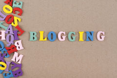 BLOGGING Wort auf dem hölzernen Hintergrund, der von buntem ABC-Alphabet verfasst wird, blockieren hölzerne Buchstaben, Kopienrau Stockbild