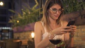 Blogginger do alimento da jovem mulher que faz a foto ao dinning no café elegante Mulher bonita que usa o assento móvel na tabela filme