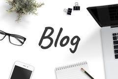 Blogtekst op bureau met blocnote, laptop computer, smartphone, potlood, klemmen, glazen, installatie wordt omringd die stock foto's