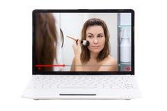Blogue da beleza - a exibição da jovem mulher como aplicar-se compõe no portátil fotografia de stock
