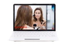 Blogue da beleza - a exibição da jovem mulher como aplicar-se compõe no vídeo na tela do portátil foto de stock