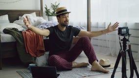 Blogue video da gravação do blogger da forma do homem novo sobre a roupa na câmera e fala aos seguidores em casa imagem de stock royalty free