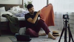 Blogue video da gravação do blogger da forma do homem novo sobre a roupa na câmera e fala aos seguidores em casa imagens de stock
