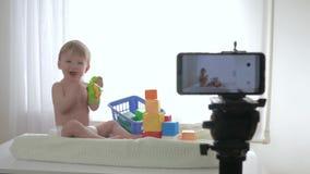 Blogueando, el bebé sonriente feliz está jugando con los juguetes y las manos que aplauden mientras que escribe en línea fluir vi almacen de metraje de vídeo