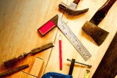 Blokhaak, houten potlood, hamer, zaag, klem, Beitel, bankschroef, meetlint, dossier voor timmerman op houten achtergrondhulpmidde stock afbeeldingen