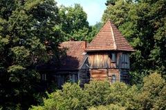 Blokhuis als een klein die kasteel en met behoefte aan restauratie wordt met lange bomen wordt omringd gevormd die royalty-vrije stock afbeelding