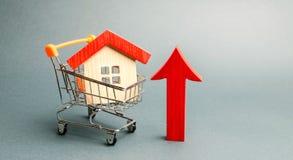 Blokhuis in een supermarktkarretje en een rode pijl omhoog Het concept het verhogen van de kosten van huisvesting Hoge vraag naar stock afbeeldingen