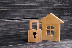 Blokhuis met een hangslot Huis met een slot Veiligheid en veiligheid, zakelijk onderpand, lening voor een hypotheek Inbeslagnemin stock foto's