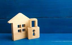 Blokhuis met een hangslot Huis met een slot Veiligheid en veiligheid, zakelijk onderpand, lening voor een hypotheek Inbeslagnemin stock afbeelding
