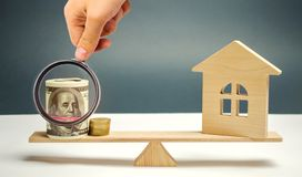 Blokhuis met geld op de schalen Het concept onroerende goederenaankoop Verkoop van bezit Betaling van de hypotheek afkoop royalty-vrije stock afbeeldingen