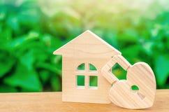 Blokhuis met Hart gevormd slot op een groene bokehachtergrond Liefdenest, verhoudingen Het kopen van een huis met een jonge famil stock foto's