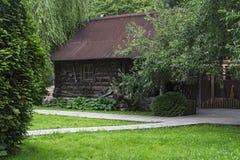 Blokhuis van logboeken onder bomen wordt gemaakt die Royalty-vrije Stock Fotografie