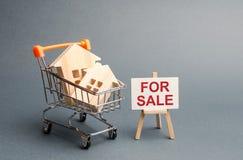 Blokhuizen in een handelkar en een tribune met inschrijving VOOR VERKOOP Verkoop van huizen en onroerende goederen Grote kortinge stock foto's