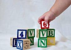 Blokken en babyhand Stock Afbeeldingen