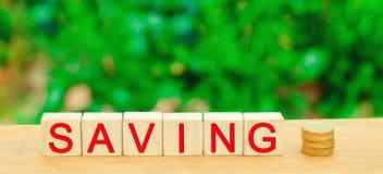 Blokken met de inschrijvings` Besparing ` en muntstukken Het concept investering in een bedrijfsproject, de aankoop van onroerend royalty-vrije stock fotografie