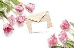Blom- bakgrund med tulpanblommor och det kraft kuvertet Lekmanna- lägenhet, bästa sikt Älskvärt hälsa kort med tulpan för moderda arkivfoton
