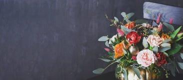 Blom- bukett för höst i punpkinvas på svart stol, baner arkivbild