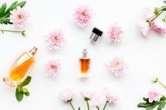 Blom- doft för kvinnor Flaska av doft nära delikata rosa blommor på den vita modellen för bästa sikt för bakgrund fotografering för bildbyråer
