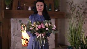 Blom- konstnär för yrkesmässig kvinna, blomsterhandlare i blåa klänningperfoms den selfmade härliga buketten av olika rosor och lager videofilmer