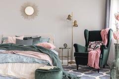 Blom- kudde och rosa filt på den gröna bekväma fåtöljen för smaragd i trendigt sovrum arkivfoto