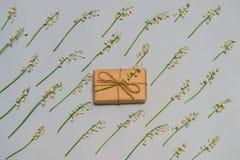 Blom- modell av liljekonvaljblommor på ljus pastellfärgad bakgrund med gåvaasken som slås in i kraft papper Hälsningkort för royaltyfri fotografi