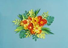 Blom- ordning av pappers- blommor på en blå bakgrund tropiska blommaleaves Gulna, göra grön, apelsinen och blått, rött Royaltyfri Foto