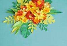 Blom- ordning av pappers- blommor på en blå bakgrund tropiska blommaleaves Gulna, göra grön, apelsinen och blått, rött Arkivbilder