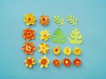 Blom- ordning av pappers- blommor på en blå bakgrund tropiska blommaleaves Gulna, göra grön, apelsinen och blått, rött Royaltyfria Bilder