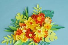 Blom- ordning av pappers- blommor på en blå bakgrund tropiska blommaleaves Gulna, göra grön, apelsinen och blått, rött Arkivfoto