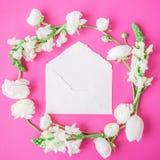 Blom- ram som göras av vita blommor, knoppar och det vita kuvertet på rosa bakgrund Lekmanna- lägenhet, bästa sikt Fotografering för Bildbyråer