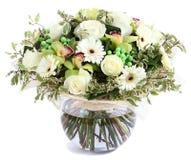 Blom- sammansättning i exponeringsglas, genomskinlig vas: Vita rosor, orkidér, vita gerberatusenskönor, gröna ärtor. Isolerat på v Arkivbilder