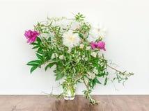 Blom- sammansättning med vita och purpurfärgade pioner i en Glass vas Royaltyfri Bild