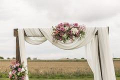 Blom- träbåge med den vita torkduken och nya violetta rosa vita blommor med gröna sidor på en lantlig bröllopceremoni arkivfoton