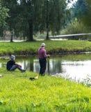 Blome/Letland - Augustus twintigste, 2018: Foto van Twee Millennials die - het Besteden KwaliteitsVrije tijd vissen stock fotografie