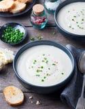 Blomkål kräm- soppa för potatis med salladslöken i svart bunke på träbakgrund royaltyfria foton