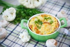 Blomkål som bakas med ägget och ost Arkivbild