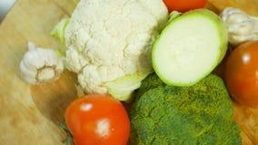 Blomk?l, zucchini, tomat, broccoli och vitl?k som roterar p? en tr?sk?rbr?da 4K stock video