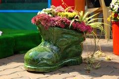Blomkruka i form av skon med blommor Royaltyfria Bilder