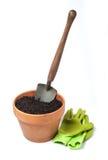 Blomkruka med den trädgårds- skyffeln och handskar Arkivbild